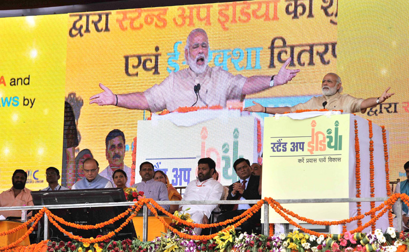 The Prime Minister, Shri Narendra Modi addressing at the launch of 'Stand Up India' and e-Rickshaw distribution programme, in Noida, Uttar Pradesh on April 05, 2016. 	The Union Minister for Finance, Corporate Affairs and Information & Broadcasting, Shri Arun Jaitley and the Minister of State for Human Resource Development, Prof. (Dr.) Ram Shankar Katheria are also seen.